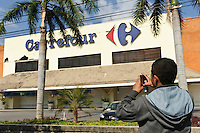 A man photographing earthquake damage at Carrefour, Jalan Sunset, Kuta, Bali, Indonesia, 13/10/11.