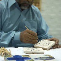 Traditional craft worker  painting the famous turquoise tiles of Multan, Pakistan<br />