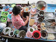 Woman preparing food on a boat at the Taling Chan Floating Market in Bangkok, Thailand. Floating kitchen!