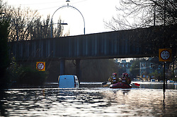 © Licensed to London News Pictures. 27/12/2015. York, UK.  A mountain rescue team in a boat pass a car submersed in flood water on Huntingdon Road in York. Large areas of the North of England have been hit by severe flooding following unusually heavy rainfall in December. Photo credit: Ben Cawthra/LNP