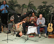 Brazilian dancer Gustavo Caldas flies through the air as musicians, including Pete Seeger at right, applaud during a benefit concert for Save Them Now at the Pointe of Praise Family Life Center in Kingston on Monday, Jan. 18, 2010. Save Them Now is a re-entry program for men returning to Ulster County from incarceration or long-term drug treatment programs.