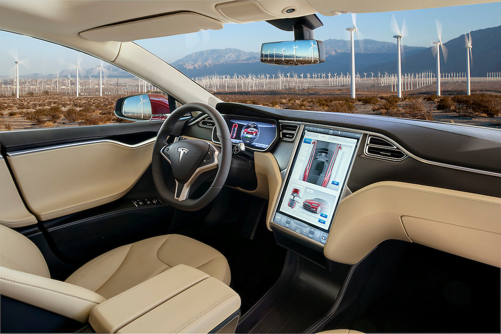 two tone tan and cream Interior of a  Red 2015 Tesla Model S P85+ photographed amongst the power generating windmills of Palm Springs, CA