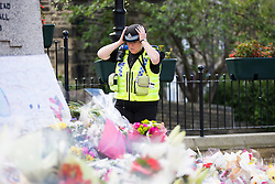 © Licensed to London News Pictures. 22/06/2016. Birstall UK. On what would have been MP Jo Cox's 42nd birthday a police community support officer look at the sea of flowers left in Birstall market square near the scene where MP Jo Cox was murdered last week. Photo credit: Andrew McCaren/LNP