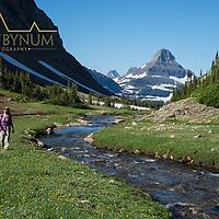 alpine meadow woman hiking along siyeh creek glacier national park