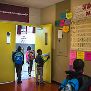 WASHINGTON, DC - APR 24:  Students arrive at Simon Elementary School in Washington, DC, under a banner encouraging school attendance, April 24, 2014. DC has enormous truancy rates, even among young children. In the last year or two, the school system has made a big push to improve attendance. Simon Elementary is seen as a model, introducing incentives and games that are tied to attendance and meant to get kids excited about coming to school; systems to ensure that parents get a call home whenever their kids are absent; weekly attendance meetings to talk about kids who are missing too much school; and a partnership with a community based organisation that can make home visits and connect families with services. (Photo by Evelyn Hockstein/For The Washington Post)