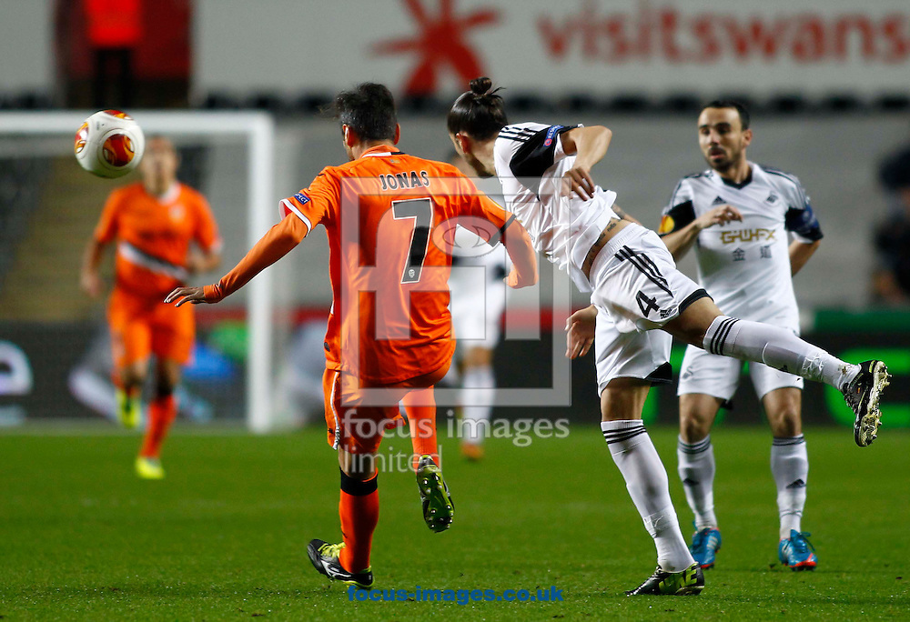 Picture by Mike  Griffiths/Focus Images Ltd +44 7766 223933<br /> 28/11/2013<br /> Chico Flores of Swansea City and Jonas of Valencia Club de F&uacute;tbol during the UEFA Europa League match at the Liberty Stadium, Swansea.