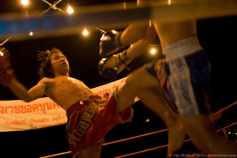 Young Mui Thai kick boxers compete at a small fair near Chiang Mai, Thailand.