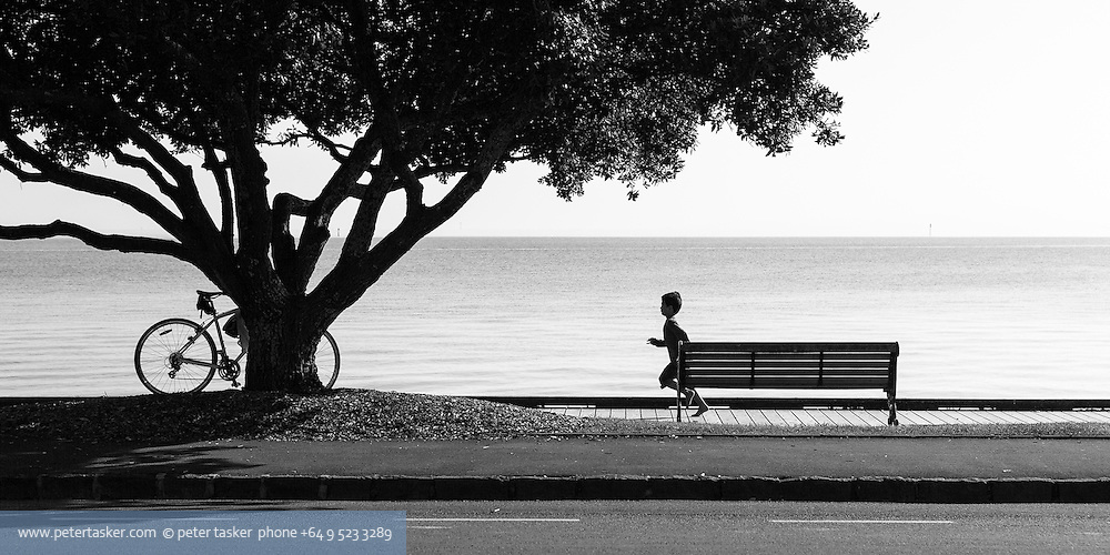 Boy running along boardwalk at St Heliers Bay, Tamaki Drive, Auckland.