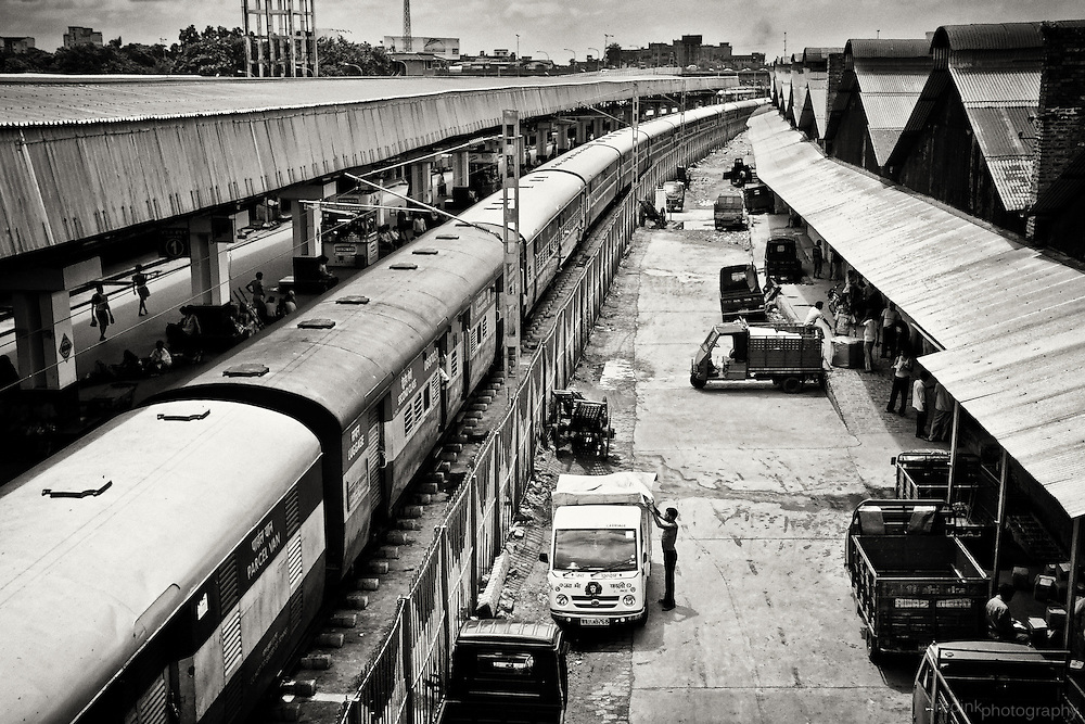 A train waits for passengers to board. Warehouse laborers at work. Howrah Station, Kolkata (Calcutta), India. Converted to black and white using Silver Efex Pro.