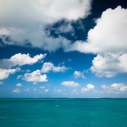 The turquoise waters of the Caribbean lie below cloud-dotted azure skies.