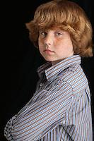 Boy (10-12) on black background portrait