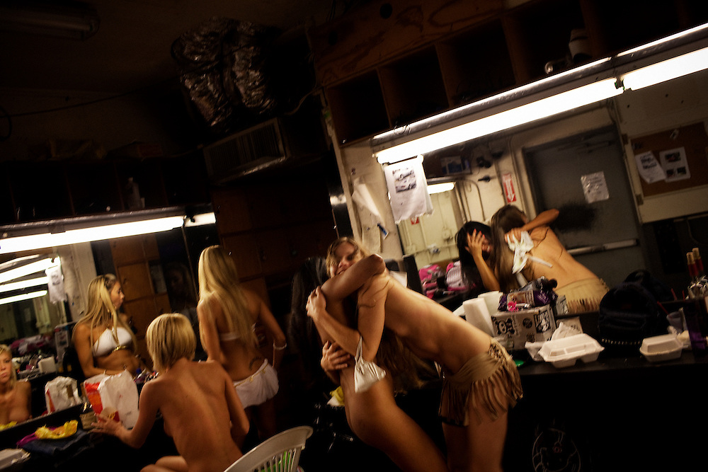 """""""Anya"""" embraces a friend in the dressing room as girls prepare for her turn to dance at the world famous Mons Venus strip club in Tampa, Florida."""