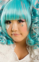 Close-up portrait of young woman with blue hair dressed as a doll