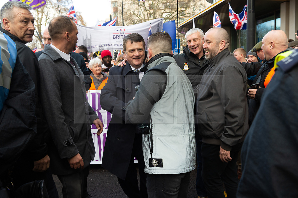 © Licensed to London News Pictures. 09/12/2018. London, UK. Leader of UKIP Gerard Batten shakes hands with former English Defence League founder Tommy Robinson before a pro-Brexit march, organised by UKIP. The march took place three days before parliament's crucial vote on Theresa May's deal.<br /> . Photo credit: Ray Tang/LNP