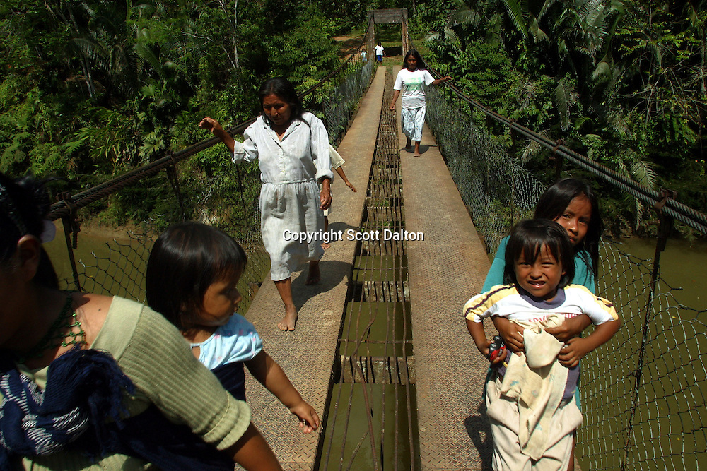 Kichwa indians cross a bridge in Sarayaku, a small Indian village deep in Ecuador's Amazon region on Sunday, October 26, 2003. The community of Sarayaku is against any attempt to look for oil on their territory because they say it will destroy the jungles that provide them with their food. Nevertheless the Ecuadorian government and foreign oil companies are determined to explore for oil in Ecuador's Amazon region. (Photo/Scott Dalton)