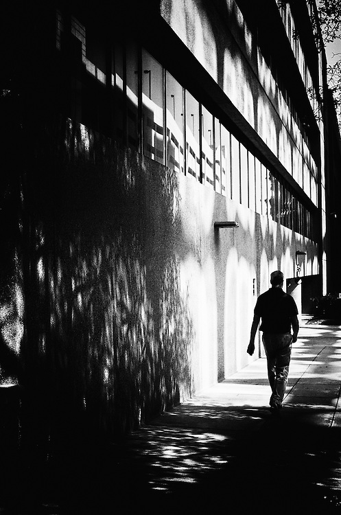 Silhouette of a man walking down a sidewalk with shadows being cast on the sidewalk and the building next to him..