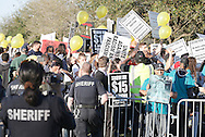 Police watch as people protest the Republican Presidential Debate at the University of Houston in Houston, Texas on February 25, 2016.