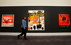 "© Licensed to London News Pictures. 07/02/2020. London, UK. A staff member walks in front of Banksy's painting titled 'Vote to Love' (Est £400,000 - £700,000) (L), Jean-Michel Basquiat's painting titled 'Rubber' (Est. £6-£8 million) (C) and Kerry James Marshall's painting titled ""Draw Me' (Est£1.5 - £2 million) (R) at the preview of Sotheby's Contemporary Art. The auction will take place at Sotheby's in central London on 11 and 12 February 2020. Photo credit: Dinendra Haria/LNP"