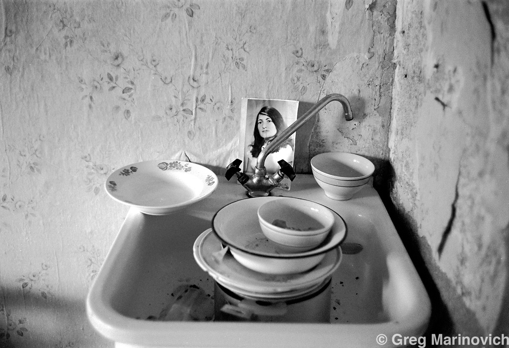 IPMG0831 Grozny, Chechnya, 1995: Dirty dishes and a photograph of the owner of a Grozny apartment in the capital of Chechnya, July 1995.  Russia agreed to grant autonomy after Chechens retook several towns and the capital Grozny in 1995, after a bloody war for Chechen independence that saw the capital devastated by massive continued Russian bombing.  The Chechens are Moslem and have a strong sense of national identity.  Their fight for independence from Russia has increased an Islamic militancy and  identity. <br /> Photograph by Greg Marinovich/South Photographs