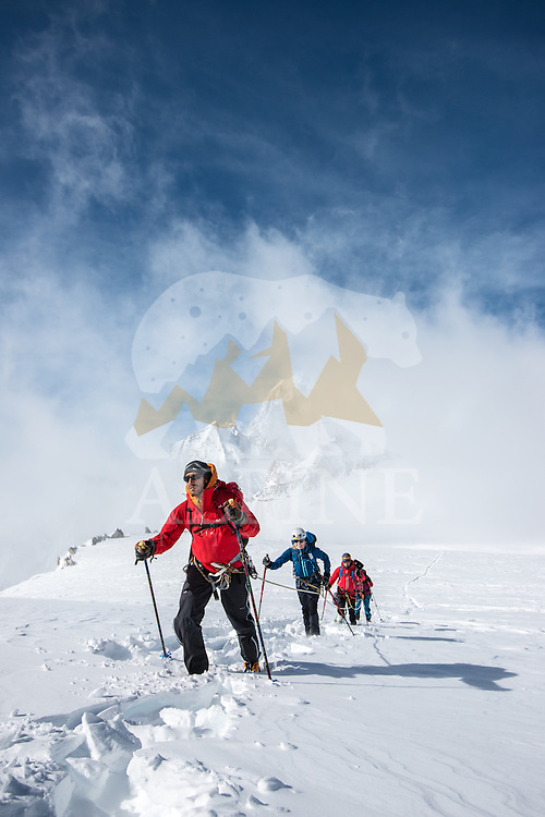 A front-view perspective on a team of four mountaineers traversing Glacier Blanche with a view on Pointe Helbroner in the background.