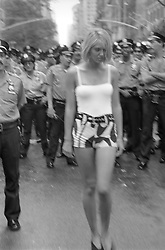 woman in shorts walking in a crowd of police officers