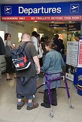 Young couple queuing to go into the departure lounge at airport,