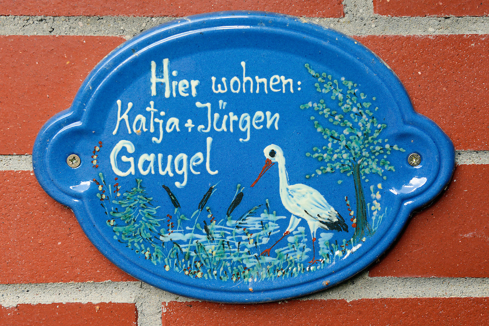 Family name sign with white stork symbol on their house, Oder river delta/Odra river rewilding area, Stettiner Haff, on the border between Germany and Poland