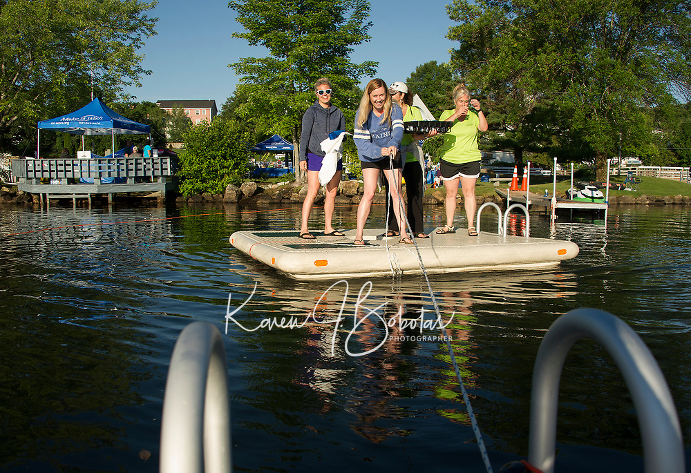 """Nikki Lyons Lahey and Holly Blanchard from Make A Wish with volunteers Maria Armano and Wendy Keenan bring provisions out to rafters during the Make A Wish """"Rafting for Wishes"""" event on Saturday at Hesky Park.  (Karen Bobotas/for the Laconia Daily Sun)"""