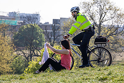 © Licensed to London News Pictures. 15/04/2020. London, UK. A Police cyclist patrols Primrose Hill in North London as a women relaxes on the grass as Ministers decide when and how the lockdown will finish as politicians are warned that the UK could face the worst recession in 300 years. Photo credit: Alex Lentati/LNP