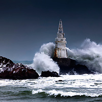 Big waves are smashing into a lighthouse