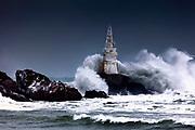 Big waves are smashing into a lighthouse