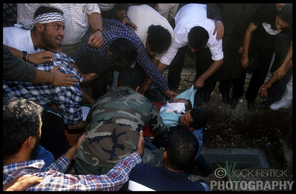 Palestinians lower the body of Hani Marzouk, 38, into a grave in the West-bank city of Jenin. Marzouk, was wounded during clashes with Israeli soldiers in Nablus and died the following day. He was brought to his hometown of Jenin for his funeral approximately 100 kilometers North of Jerusalem. (Photo © Jock Fistick)