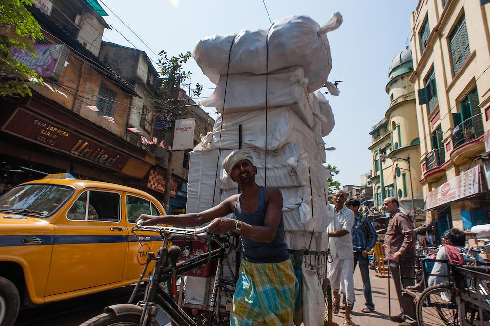 Man carrying goods in bicycle in Kolkata (India).
