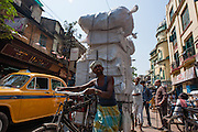 Man carrying goods in bicycle in Kolkata (India).