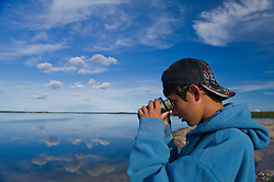"""Brendan Felix Head, 14, watches birds in The Thelon, the largest and most remote game sanctuary in North America, which almost no one has heard of.  For the Akaitcho Dene, the Upper Thelon River is """"the place where God began.""""  Sparsely populated, today few make it into the Thelon. Distances are simply too far, modern vehicles too expensive and unreliable. For the Dene youth, faced with the pressures of a western world, the ties that bind the people and their way of life to the land are even more tenuous. Every impending mine, road, and dam construction threatens to sever these connections. In July and August, 2011 a group of youth paddled to their ancestral hunting ground and spiritual abode.  this next generation of young leaders will be the ones who will need to speak for the Thelon the loudest. (Photo by Ami Vitale)"""