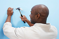 Man Hammering Nail Into Wall