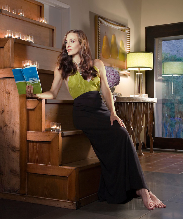 """woman in long black dress reading book """"cradle to cradle"""" while sitting on stair case."""