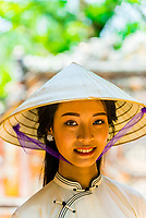 Vietnamese woman wearing the traditional ao dai costume in the Imperial City, a walled palace within the citadel of the city of Huế which is the former imperial capital of Vietnam. Hue, Central Vietnam.