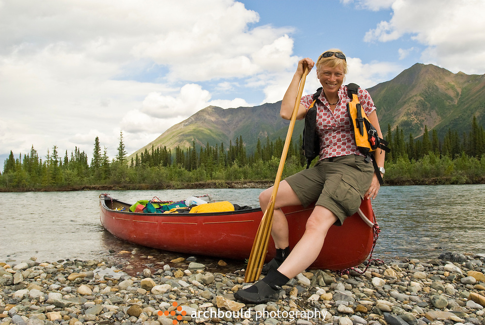 A canoeist takes a break on the Wind River, Yukon, Canada.<br /> <br /> NOT IN YOUR BUDGET? Contact Cathie for a price specific to your project.