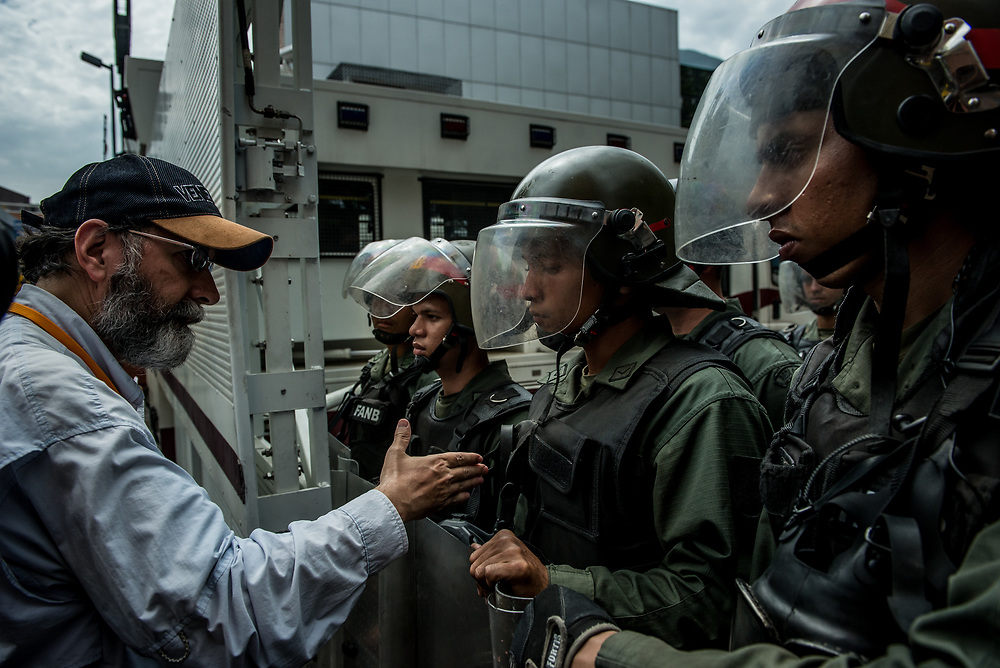 CARACAS, VENEZUELA - JUNE 2, 2017: A man tries to shake the hand of a soldier blocking the street so that anti-government protesters could not pass. The soldier refused to shake his hand.  The streets of Caracas and other cities across Venezuela have been filled with tens of thousands of demonstrators for nearly 100 days of massive protests, held since April 1st. Protesters are enraged at the government for becoming an increasingly repressive, authoritarian regime that has delayed elections, used armed government loyalist to threaten dissidents, called for the Constitution to be re-written to favor them, jailed and tortured protesters and members of the political opposition, and whose corruption and failed economic policy has caused the current economic crisis that has led to widespread food and medicine shortages across the country.  Independent local media report nearly 100 people have been killed during protests and protest-related riots and looting.  The government currently only officially reports 75 deaths.  Over 2,000 people have been injured, and over 3,000 protesters have been detained by authorities.  PHOTO: Meridith Kohut