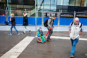 Een jongetje wordt bij station Utrecht zittend op een koffer voortgetrokken door zijn vader.<br /> <br /> A boy sitting on a suitcase is being pulled by his father at Utrecht Central Station