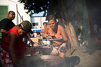 Residents cook feijoada in Complexo da Mare, Rio de Janeiro, Brazil, on Saturday, April 27, 2013. Complexo da Mare, is a complex of 16 communities, in the north zone of Rio de Janeiro. It is the largest complex of favelas with 130,000 residents. It is targeted for pacification as the city prepares for the 2014 World Cup and the 2016 Olympics. Four factions run the complex -  three drug gangs and the militia. The rival gangs fight for control of the drug trade. Although crime is low in the favelas by rule  of law enforced by the gangs, cross-fire shootings and gang violence is often high. Neighborhood associations are an integral part of community development within Mare, making up for a lack of government assistance.