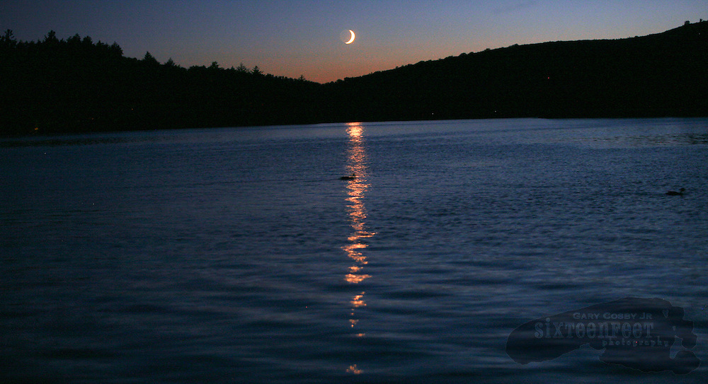 The crescent moon sets over Tupper Lake in the Adirondack Park near the town of Tupper Lake, New York just after sundown.  Photo by Gary Cosby Jr.