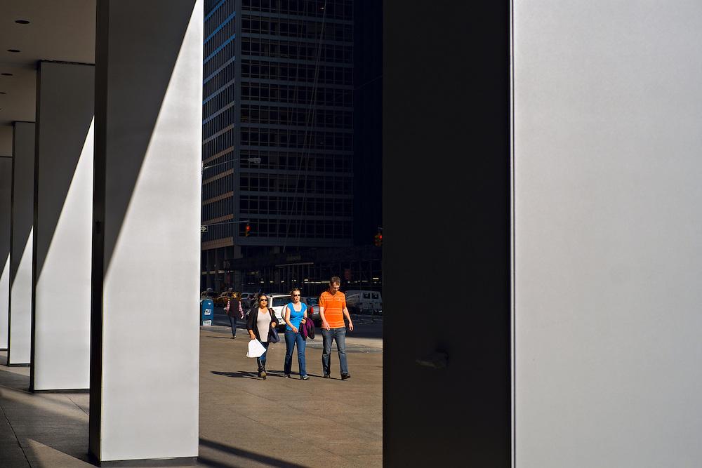 Trhee people walking on sidewalk