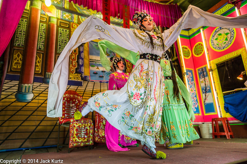 "28 JANUARY 2014 - BANGKOK, THAILAND: Members of the Tear Kia Ee Lye Heng opera troupe perform in Bangkok. They were performing for a business in the Min Buri district of Bangkok for the Lunar New Year, which this year is Jan 31. Chinese opera was once very popular in Thailand, where it is called ""Ngiew."" It is usually performed in the Teochew language. Millions of Teochew speaking Chinese emigrated to Thailand (then Siam) in the 18th and 19th centuries and brought their cultural practices with them. Recently the popularity of ngiew has faded as people turn to performances of opera on DVD or movies. There are still as many 30 Chinese opera troupes left in Bangkok and its environs. They are especially busy during Chinese New Year when they travel from Chinese temple to Chinese temple performing on stages they put up in streets near the temple, sometimes sleeping on hammocks they sling under their stage. They are also frequently hired by Chinese owned businesses to perform as a form of merit making.    PHOTO BY JACK KURTZ"
