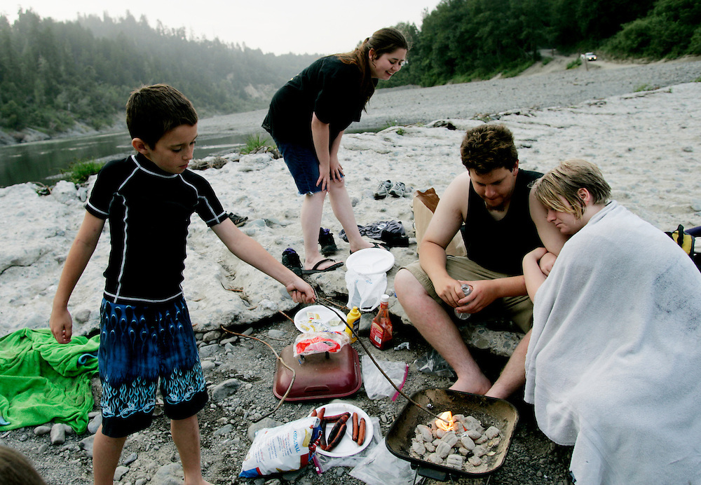 From left, Cory Hall, 8, Patricia Johnson, 17, Javan Saffell, and Sami Frye, 17, enjoy a barbecue along the Eel River in Scotia, CA on Tuesday, June 27, 2006. The Halls are the fourth generation of their family to grow up in Scotia. The town of Scotia in Northern California is a company town owned by the Pacific Lumber Company (PALCO), but that will change as the company will begin to sell the town. (Photo by Max Whittaker for The New York Times)<br />