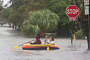 Young women paddle down a flooded street in the historic district as Hurricane Joaquin brings heavy rain, flooding and strong winds as it passes offshore October 3, 2015 in Charleston, South Carolina.