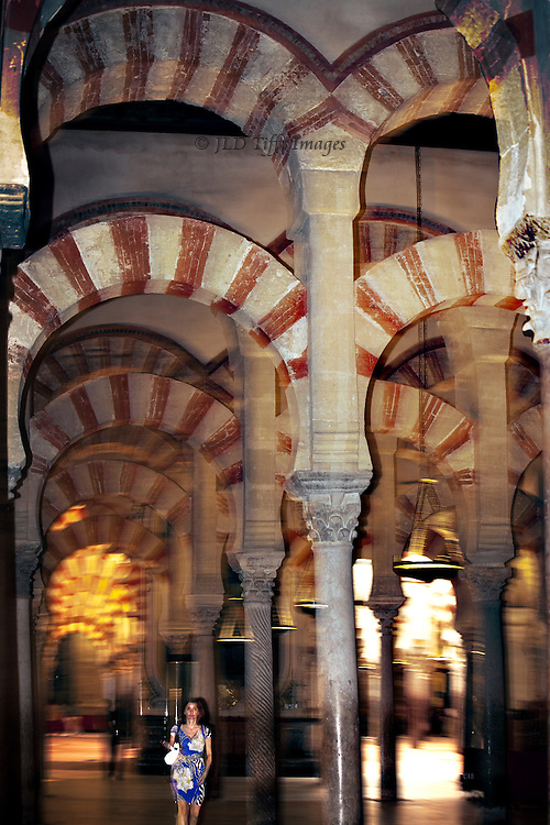 Interior of the Mezquita, or Grand Mosque of Cordoba, showing a woman tourist walking through the forest of columns and giving it scale.  Flash exposure stops her motion while the arches above are slightly blurred.