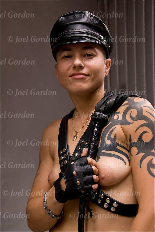 Semi-nude, bare breasted in S&amp;M leather gear and whip with tribal tattoos.  Before the start of the Pride Parade in NYC. <br />