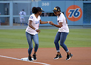 Jun 13, 2018; Los Angeles, CA, USA; Deanna Hill (3) hands a baseball off to Kendall Ellis (4) during a ceremonial relay before a MLB game between the Texas Rangers and the Los Angeles Dodgers at Dodger Stadium. Hill and Ellis ran the third and fourth legs of the Southern California Trojans women's 4 x 400m relay that won the NCAA title in the final even to win  the national team title.